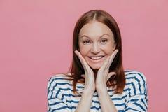 Το Headshot της ελκυστικής νέας γυναίκας αγγίζει τα μάγουλα και με τους δύο φοίνικες, έχει το ειλικρινές χαμόγελο, φορά το περιστ στοκ εικόνες με δικαίωμα ελεύθερης χρήσης