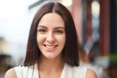 Το Headshot της ευχάριστης κοιτάζοντας γοητευτικής χαμογελώντας νέας γυναίκας με το υγιές δέρμα, σκοτεινή τρίχα, που είναι στην κ στοκ φωτογραφία με δικαίωμα ελεύθερης χρήσης