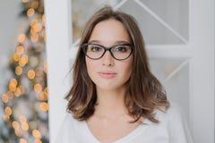 Το Headshot του καλού νέου θηλυκού προτύπου στα διαφανή γυαλιά, ντύνει τη σκοτεινή τρίχα, στα περιστασιακά ενδύματα, απολαμβάνει  στοκ εικόνα με δικαίωμα ελεύθερης χρήσης