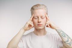 Το Headshot του νεαρού άνδρα κρατά τα δάχτυλα στους ναούς Στοκ Εικόνα