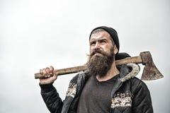 Το Hipster με τη γενειάδα στο σοβαρό πρόσωπο φέρνει το τσεκούρι στον ουρανό ώμων στο υπόβαθρο, διάστημα αντιγράφων Υλοτόμος βάναυ Στοκ Φωτογραφία