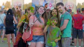 Το Holi, άνθρωποι ομάδας στη φωτεινή σκόνη κάνει τη φωτογραφία selfi σε αρρενωπό σε υπαίθριο, η οικογένεια με την τρίχα χρώματος  φιλμ μικρού μήκους