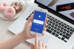 Το iPhone εκμετάλλευσης γυναικών 6S αυξήθηκε χρυσός με την κοινωνική υπηρεσία Facebook Στοκ Εικόνες