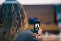 Το iPhone Χ της Apple πηγαίνει στην παγκόσμια γυναίκα πώλησης που δοκιμάζει την ταυτότητα προσώπου Στοκ Φωτογραφία