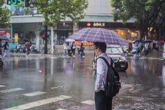 Το It's που βρέχουν το πρωί, και οι πεζοί που περπατούν μέσω του δρόμου περνούν από τη διατομή στοκ εικόνα με δικαίωμα ελεύθερης χρήσης