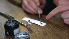 Το Jeweler παίρνει το σμάλτο για τη ζωγραφική του ασημένιου δαχτυλιδιού με ένα εργαλείο απόθεμα βίντεο