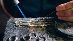 Το Jeweler, χρυσοχόος σε ένα επαγγελματικό εργαστήριο κοσμήματος ενώνει στενά μια αλυσίδα μετάλλων σε ένα κατάστημα κοσμημάτων απόθεμα βίντεο