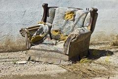 Το Junked, και κατέστρεψε η επικαλυμμένη καρέκλα έτοιμη να ληφθεί στα υλικά οδόστρωσης Στοκ Φωτογραφία
