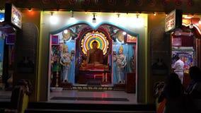 Το Kataragama, Σρι Λάνκα - 2019-03-29 - άγαλμα του Βούδα υποστηρίζεται από τη φανταχτερή ελαφριά επίδειξη φιλμ μικρού μήκους