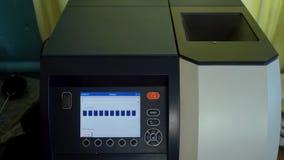 Το Laborer πιέζει ένα κουμπί στη ηλεκτρονική συσκευή για να αναλύσει την ποιότητα των συγκομιδών φιλμ μικρού μήκους
