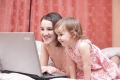 το lap-top κορών κοιτάζει mum Στοκ φωτογραφία με δικαίωμα ελεύθερης χρήσης