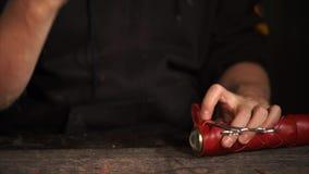 Το Leatherworker σφίγγει τη ζώνη σε ένα περίβλημα δέρματος του καλειδοσκόπιου απόθεμα βίντεο