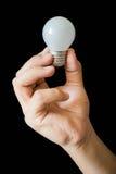 Το Lightbulb κράτησε υπό εξέταση στο μαύρο υπόβαθρο Στοκ φωτογραφίες με δικαίωμα ελεύθερης χρήσης