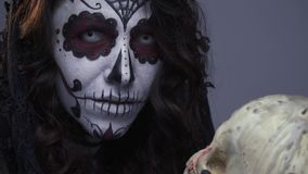 Το Makeup για αποκριές, ένα κορίτσι με μορφή ενός κρανίου ζάχαρης κρατά ένα ανθρώπινο κρανίο στο χέρι της φιλμ μικρού μήκους