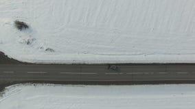 Το mashine καθαρίσματος χιονιού καθαρίζει έναν δρόμο στο χιονισμένο χειμερινό τομέα με τα αυτοκίνητα και τα φορτηγά Εναέριος κάθε απόθεμα βίντεο