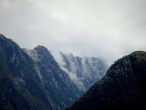 Το Milford ηχεί τα σύννεφα πέρα από τα φιορδ Στοκ Φωτογραφία
