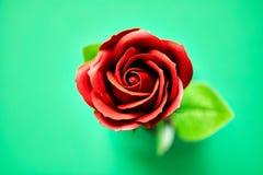 Το Minimalistic τεχνητού ενός κόκκινου αυξήθηκε εικόνα που φωτογραφίστηκε στο στούντιο που απομονώθηκε σε πράσινο στοκ εικόνες