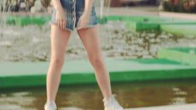 Το Modernly έντυσε το κορίτσι στο υπόβαθρο της πηγής πόλεων στα υψηλά πνεύματα απόθεμα βίντεο