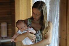 Το Mom αγκαλιάζει το μωρό της στα όπλα της στοκ φωτογραφίες