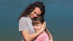 Το Mom αγκαλιάζει την κόρη της από τον ποταμό Ένα μικρό κορίτσι με τη μητέρα της από το νερό Οικογένεια υπαίθρια απόθεμα βίντεο