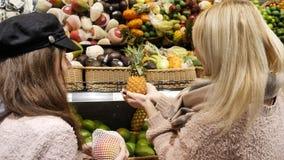 Το Mom αγοράζει τα υγιή τρόφιμα με την κόρη της στην υπεραγορά, επιλέγει τον κίτρινο ανανά φιλμ μικρού μήκους