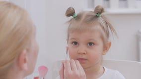 Το Mom βάζει τη σκόνη στο πρόσωπο της λίγη κόρη με μια βούρτσα απόθεμα βίντεο
