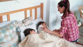 Το Mom βάζει τις κόρες στο κρεβάτι, τις φιλά, επιθυμεί τα καλά όνειρα, σε αργή κίνηση απόθεμα βίντεο