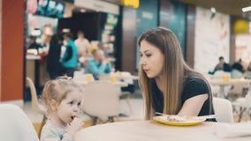 Νέα όμορφη μητέρα με την λίγη συνεδρίαση κορών σε έναν καφέ Το Mom δίνει στην κόρη της ένα ποτό μέσω του αχύρου φιλμ μικρού μήκους