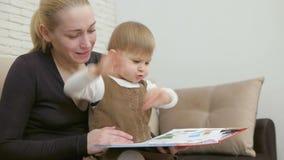 Το Mom διαβάζει το βιβλίο της μικρής συνεδρίασης κορών του στον καναπέ στο καθιστικό απόθεμα βίντεο