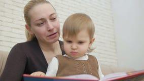 Το Mom διαβάζει το βιβλίο της μικρής συνεδρίασης κορών του στον καναπέ στο καθιστικό φιλμ μικρού μήκους