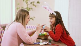Το Mom διακοσμεί το αυγό, το οποίο το κορίτσι κρατά στα χέρια της και γελούν απόθεμα βίντεο