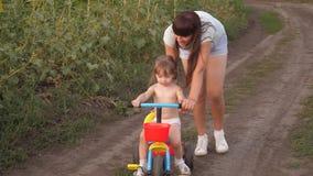 Το Mom διδάσκει την κόρη για να οδηγήσει ένα ποδήλατο Παιχνίδια αδελφών με ένα μικρό παιδί Η έννοια της ευτυχούς παιδικής ηλικίας απόθεμα βίντεο