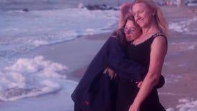 Το Mom είναι ευτυχές που η κόρη της είναι πλησίον, αγκαλιάζοντας την στη θάλασσα φιλμ μικρού μήκους