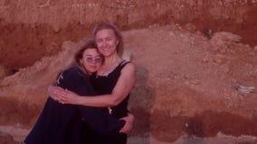 Το Mom είναι ευτυχές που η κόρη της είναι πλησίον, αγκαλιάζοντας την στη θάλασσα Βράχος του αργίλου στο υπόβαθρο απόθεμα βίντεο