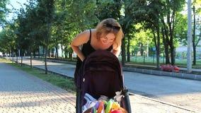 Το Mom εξετάζει στοργικά την κόρη της και την τινάζει σε έναν περιπατητή Όμορφη νέα γυναίκα με ένα παιδί φιλμ μικρού μήκους