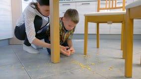 Το Mom επιπλήττει το γιο της για τα διεσπαρμένα τρόφιμα στο πάτωμα κουζινών και του κάνει καθαρό επάνω Καθαρίστε επάνω τις νιφάδε απόθεμα βίντεο