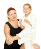 Το Mom διδάσκει την κόρη που ντύνεται σε ένα karate κιμονό λάκτισμα που μονώνεται Στοκ φωτογραφία με δικαίωμα ελεύθερης χρήσης