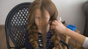 Το Mom κάνει hairstyle για ένα λυπημένο μικρό κορίτσι απόθεμα βίντεο