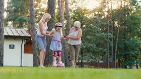 Το Mom και η γιαγιά διδάσκουν το κύλινδρος-σαλάχι που ένα κορίτσι 6 ετών, την υποστηρίζει από το χέρι Έννοια - οι πρώτες επιτυχίε απόθεμα βίντεο