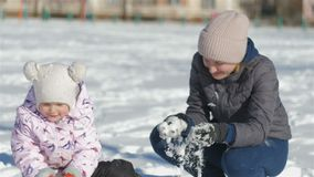 Το Mom και η κόρη έχουν τη διασκέδαση στην οδό σε όμορφο χειμερινό χιονώδες ημερησίως, η μητέρα μου ρίχνει το χιόνι στο κορίτσι,