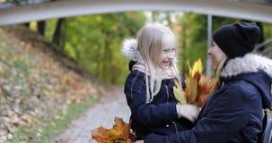 Το Mom και η κόρη αγκαλιάζουν στο πάρκο φθινοπώρου απόθεμα βίντεο