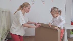 Το Mom και η κόρη ανοίγουν ένα μεγάλο κουτί από χαρτόνι με μια νέα αγορά για ένα παιδί φιλμ μικρού μήκους