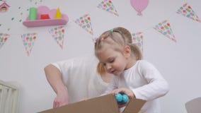 Το Mom και η κόρη ανοίγουν ένα μεγάλο κουτί από χαρτόνι με μια νέα αγορά για ένα παιδί απόθεμα βίντεο