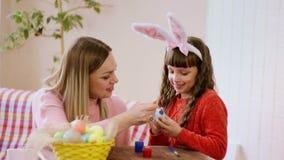 Το Mom και η κόρη διακοσμούν ένα αυγό Πάσχας με τη χαρά και ένα χαμόγελο απόθεμα βίντεο