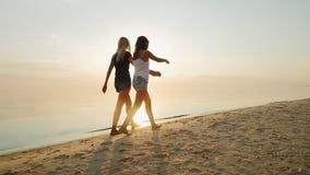 Το Mom και η κόρη είναι έφηβος στην παραλία στο ηλιοβασίλεμα υποστηρίξτε την όψη απόθεμα βίντεο