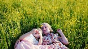 Το Mom και η κόρη είναι 6 χρονών μαζί σε μια ψηλή χλόη, επικοινωνούν Φιλική και ευτυχής οικογένεια φιλμ μικρού μήκους
