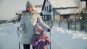 Το Mom και η κόρη εξετάζουν τη κάμερα και το χαμόγελο πριν από το σκανδιναβικό περπάτημα στα προάστια το χειμώνα φιλμ μικρού μήκους