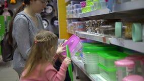 Το Mom και η κόρη επιλέγουν μαζί ένα πλαστικό καλαθάκι με φαγητό στο κατάστημα απόθεμα βίντεο
