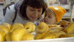 Το Mom και η κόρη επιλέγουν μαζί τα φρέσκα ψημένα αγαθά στο αρτοποιείο απόθεμα βίντεο