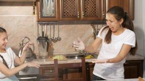 Το Mom και η κόρη εφήβων της ρίχνουν το αλεύρι ο ένας στον άλλο μαγειρεύοντας στην κουζίνα απόθεμα βίντεο